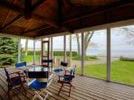The large screened in porch offers loads of seating and dining space