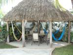 The palapa roofed patio with a table and chairs, plus several double sized hammocks