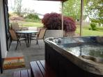 Large patio with outdoor dining table and private hot tub