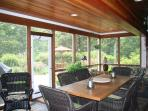 Screened porch with dininga and seeting areas, opens to patio bordered by summer gardens