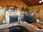 Living room with a large flat screen satellite TV/DVD, large wrap around sectional, wood burning fireplace, two leather ...