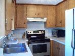 Comfortable working kitchen adjacent to dining area;, double door refrigerator/ freezer on one side.