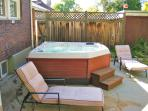 Private back yard with a premium hot tub under a pergola roof, along with a large grill