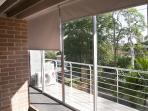 Balcony in front of the bedroom and dinning area with open wide windows and full blinders.