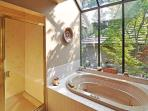 The lower level bathroom features a beautiful soaking tub with a greenhouse window into the private garden.
