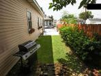 Side-yard with gas grill and gated parking