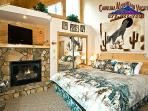 The gas log fireplace creates a warm romantic feel to the master bedroom that has a king bed and TV.