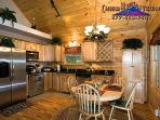 Full kitchen with stainless steel appliances, all cook ware and dining utensil and dining table.