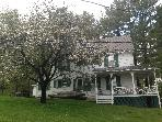 SIde view of the house with apple tree in bloom