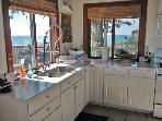 Two corner windows flanking kitchen with views; commercial faucet