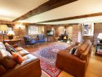 The snug at Glassonby has a cast iron log burning stove and traditional oak mullioned windows.