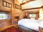 The first floor Addingham Bedroom has an antique five foot wooden carved bed and oak mullion windows