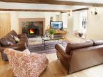 One of the three seating areas at Hause Hall Farm and the Cruik Barn with an open log burning fire
