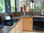 Compact, yet well-equiped kitchen. Facing south to lanai. has all the 'mod cons' except full oven.