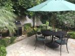 Private patio with dining area and gas grill