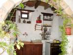 Kitchen is located off the entrance area under a hand hewn stone arch