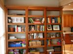 Bookcases with baskets and bins of children's paper, pens, and crafts.