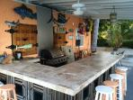 Outside bar in common area with grill and fridge