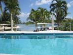 The saltwater pool located right on the beach, surrounded by palms enjoys a lovely view of the cove