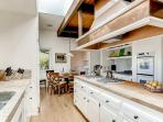 The extraordinarily well-stocked gourmet kitchen features granite countertops, city and mountain views, and a 5 burner...