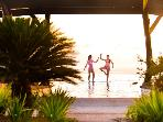 Children posing on the center wall of the infinity pool at sunset.