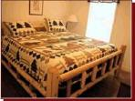 King size white cedar log bed in the master bedroom