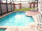The pool area has distinctive red brick pavers, and walled to the side & rear.