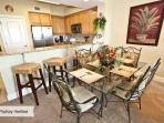 The dining area has table seating for four and three barstools.