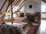 The fireplace in the upstairs living room with stripped and varnished piine beams and floor