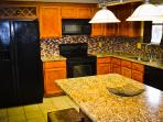Our newly-remodeled kitchen with granite countertops and tile backsplash.