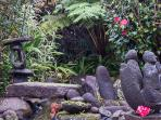 The stone sculptures enjoy the peace and beauity in the gardens of Our Home of Aloha.