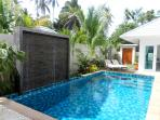 Relax in the pool to the sound of water gently,  trickiling down the water feature