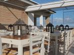 Terrazzo panoramico attrezzato con tavolini, sedie e lanterne