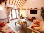 The Coach House's cosy lounge with wood-burning stove.