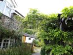 Under the pretty Wisteria arch between swimming pool and Wanws is the entrance to cosy Goat Cottage