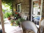 Relax in the rocking chairs on the flower draped verandah - swimming pool glimpsed through door!