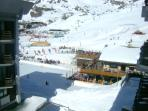 View from balcony onto ice rink, chair lifts, and 'Cretaz' ski area