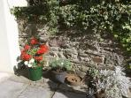 Pretty potted plants beside the front door and the old stone wall bordering the south-facing patio