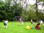 Outdoor playground with swings,slides,climbing frame,football and badminton nets,a playhouse