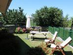 Jardín. Equipado con mesa, tumbonas y sombrillas