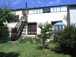 Terrasse plein sud avec porte fenêtre de la chambre et séjour, jardin clôturé avec barbecue