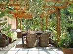 Outdoor living room where you can sit under a shady pergola.