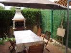 Jardín posterior con barbacoa y mobiliario de madera de teka para 6 personas y amplio parasol