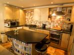 Well equipped kitchen with breakfast bar and 4 bar stools - a sociable place to enjoy a glass or 2