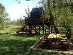 Children's play area and picnic bench in shade.