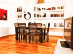 living room, wooden table, big library with books in different languages