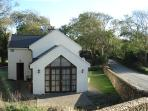 house on country lane - stone walled to front, mature setting.