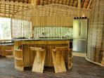 Fully equipped kitchen behind the bamboo table. A cook can be arranged if guest want