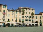 A view of the Roman Amphitheatre in the centre of Lucca. Many boutique shops, cafés and bars