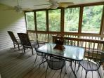 Screen porch off dining area with rocking chairs & furnished for dining.
